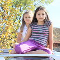 Little girls on a car barefoot kids sitting silver with tree behind Royalty Free Stock Photos