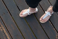 Little girls feet in white sandals a standing on the wooden deck of a jetty Stock Photography