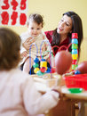 Little girls and female teacher in kindergarten Royalty Free Stock Photo