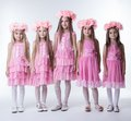 Little girls in glamour pink dresses and wreaths Stock Photos