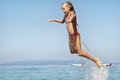Little girls jumping out of the water on sea at summer Stock Image