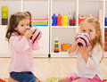 Little girls kissing the piggybanks Royalty Free Stock Photos