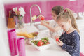 Little girls in the kitchen playing Stock Images