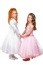 Little girls in nice dresses holding each others hands isolated on white Stock Photos