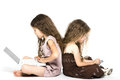Little girls playing game console back to back