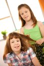 Little girls playing with hair style combing looking at camera Royalty Free Stock Photo
