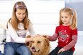 Little girls stroking dog smiling golden retriever Royalty Free Stock Photo