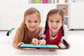 Little girls using tablet computer as artboard painting together Stock Photos