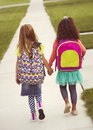 Little girls walking to school together vintage tone rear view of two holding hands as they walk along the sidewalk Royalty Free Stock Images