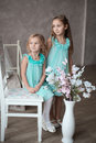 Little girls in white dresses sitting looking at you Royalty Free Stock Images