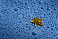 A little golden star and blue water dorops Stock Photos