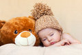 Little gorgeous baby boy with a big hat and teddy bear Stock Photos