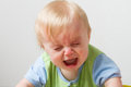 Little guy with some upset feelings young toddler crying away has his eyes closed and a huge open mouth from being so sad Stock Photos