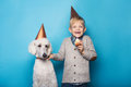 Little handsome boy with dog celebrate birthday. Friendship. Love. Cake with candle. Studio portrait over blue background Royalty Free Stock Photo