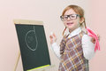 Little happy girl in glasses with pink rag chalk draws face at chalkboard studio Stock Photos