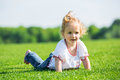 Little happy girl on a grass Stock Image