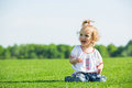 Little happy girl on a grass Stock Photos
