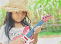 Little happy girl plays her guitar or ukulele toy Royalty Free Stock Photography