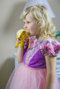 Little happy princess girl in pink dress and crown in her royal room eating banana. Royalty Free Stock Photo