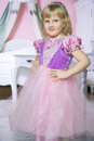 Little happy princess girl in pink dress and crown in her royal room posing and smiling. Royalty Free Stock Photo