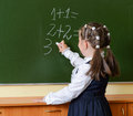 Little happy schoolgirl writing on blackboard portrait of a pretty doing arithmetics in class and smiling Stock Image