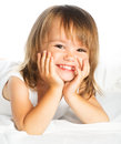 Little happy smiling cheerful girl in a bed isolated white Royalty Free Stock Images