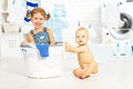 Little helpers funny kids happy sister and brother in laundry to Royalty Free Stock Photo