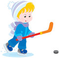 Little hockey player boy with skates stick and puck Stock Image