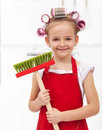 Little housekeeping fairy girl with large hair curls holding broom Stock Photo