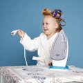 Little housewife with iron on blue background