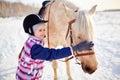Little jockey girl in helmet touching horse muzzle Royalty Free Stock Photos