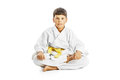 Little karate kid sitting legs crossed portrait of a boy in kimono training on the floor over white background Royalty Free Stock Photography