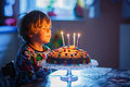 Little kid boy celebrating his birthday and blowing candles on cake Royalty Free Stock Photo