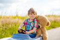 Little kid boy driving big toy car with a bear, outdoors. Royalty Free Stock Photo
