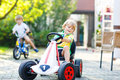 Little kid boy driving pedal car in summer garden active blond toy outdoors his brother on bike on background active leisure with Stock Photos