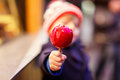 Little kid boy eating crystalized apple on Christmas market Royalty Free Stock Photo