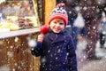 Little kid boy eating crystalized apple on Christmas market Royalty Free Stock Photo