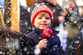 Little kid boy eating sweet apple on Christmas market Royalty Free Stock Photo
