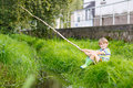 Little kid boy fishing on river with selfmade fishing rod Royalty Free Stock Photo