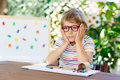 Little kid boy with glasses holding school equipment Royalty Free Stock Photo