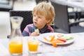 Little kid boy having healthy breakfast in hotel restaurant or c city cafe Royalty Free Stock Photos