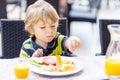 Little kid boy having healthy breakfast in hotel restaurant or c city cafe Stock Images