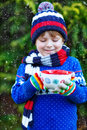 Little kid boy holding big cup with chocolate funny child snowflakes and hot cocoa and drink and marshmallows in winter sweater Stock Photos