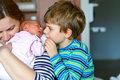 Little kid boy kissing newborn sister. Mother holding baby on arm. Royalty Free Stock Photo