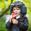 Little kid boy in pilot helmet playing with toy airplane Royalty Free Stock Photo