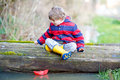Little kid boy playing with paper boat by puddle Royalty Free Stock Photo