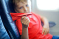 Little kid boy playing with red paper plane during flight on airplane Royalty Free Stock Photo