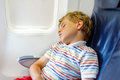 Little kid boy sleeping during long flight on airplane. Child sitting inside aircraft by a window