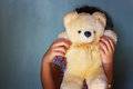Little kid hiding behind teddy bear selective focus Stock Photo