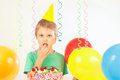 Little kid in holiday hat with birthday cake and balloons Royalty Free Stock Photo